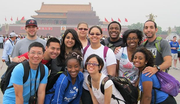 Students pose in front of the Forbidden City temple
