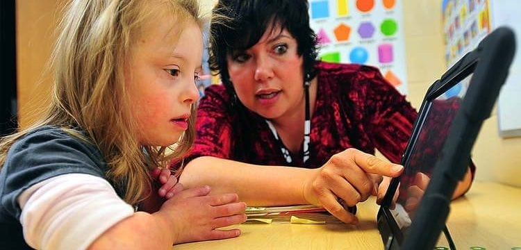 A special education child works with a teacher