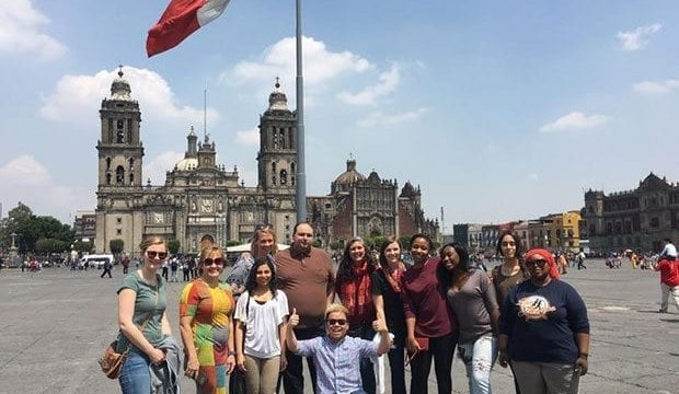Sue Kasun and study abroad students in Mexico pose in a city square