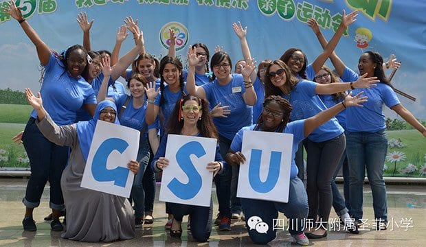 Students hold up GSU signs and pose in China
