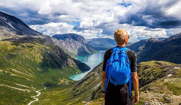 student with backpack views mountain vista in Norway