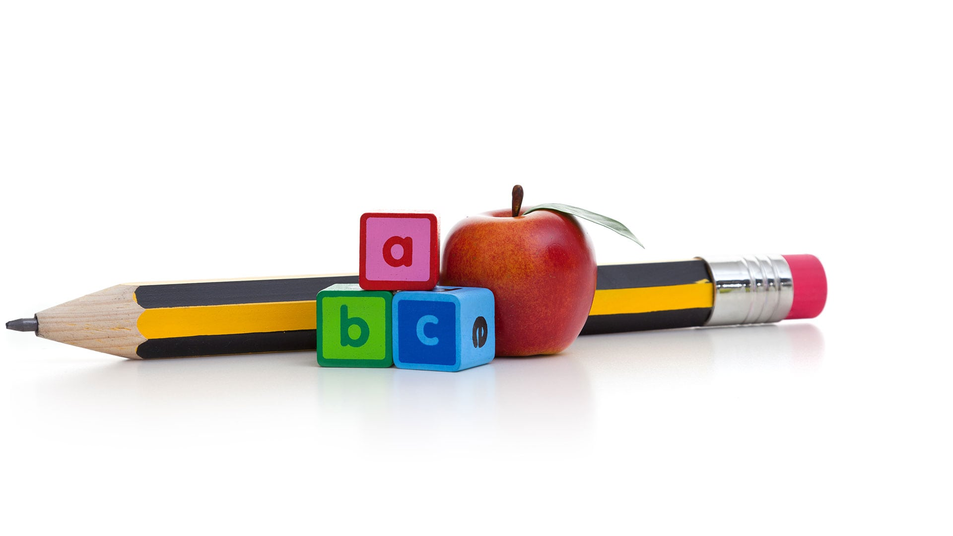 Pencil with ABC blocks and an apple against a white background