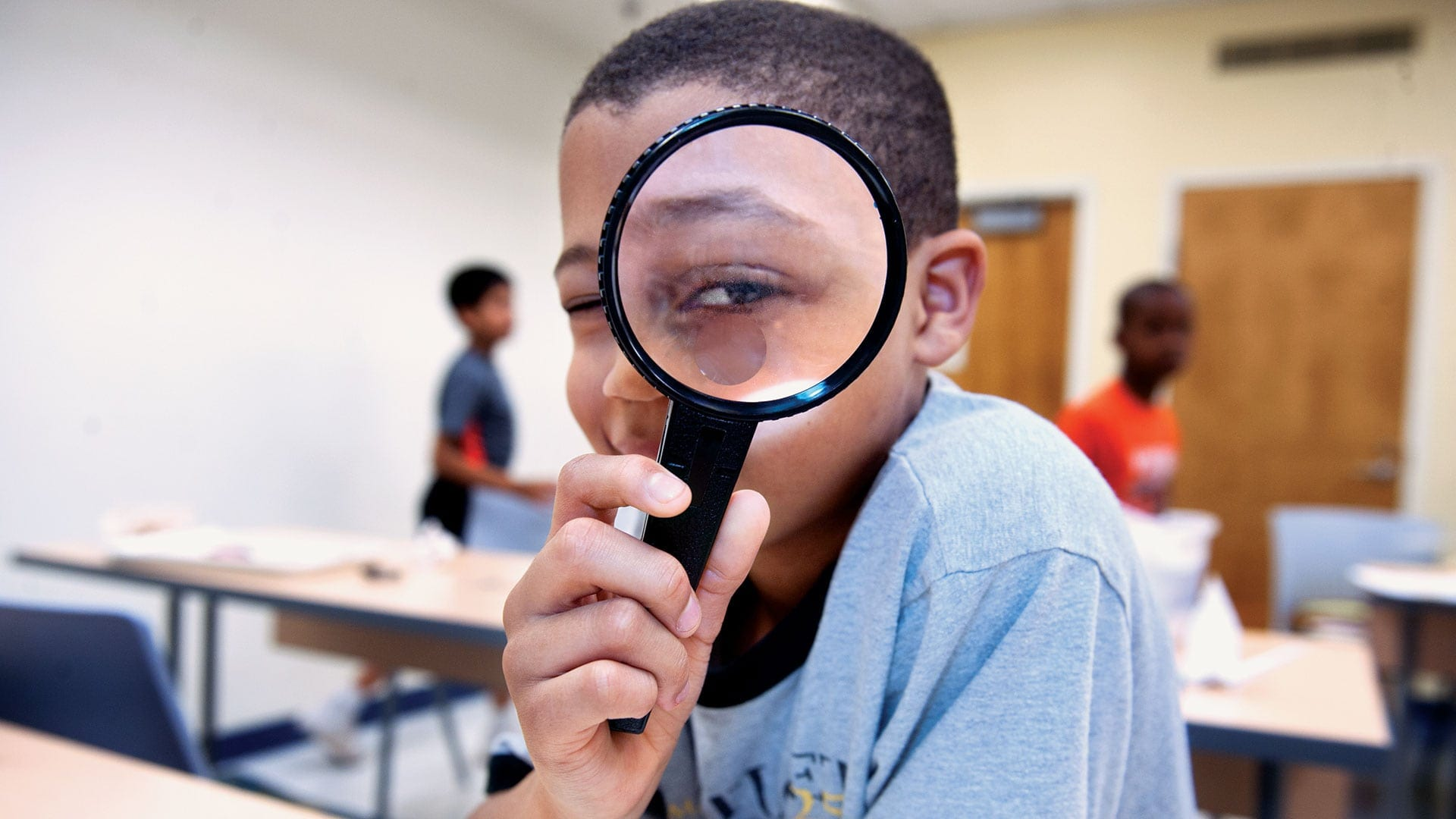 Young boy holds a magnifying glass to his eye