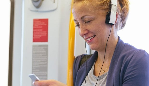 woman looks at an app while wearing assistive headphones