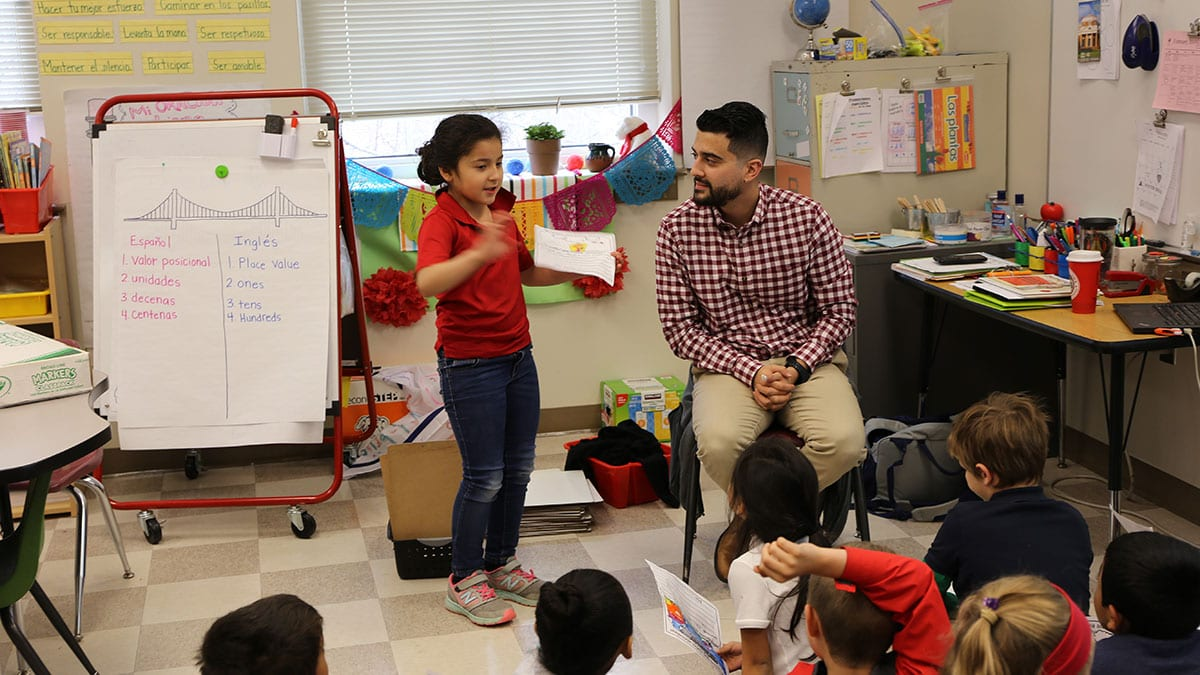 A student works with Christian Valdez in a classroom